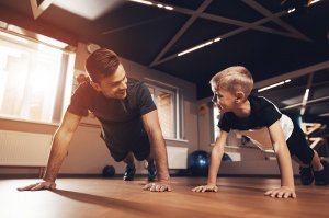 Father and son doing push ups in a home gym